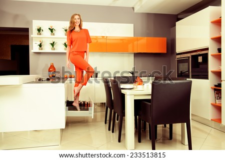 Cheerful young woman demonstrates the high quality of the kitchen furniture. Home interior. - stock photo