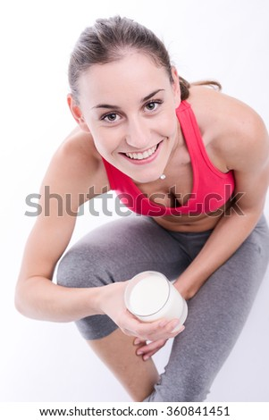 cheerful young woman drinking milk - stock photo