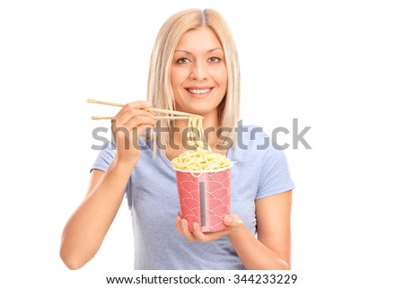 Cheerful young woman eating noodles with Chinese sticks and looking at the camera isolated on white background