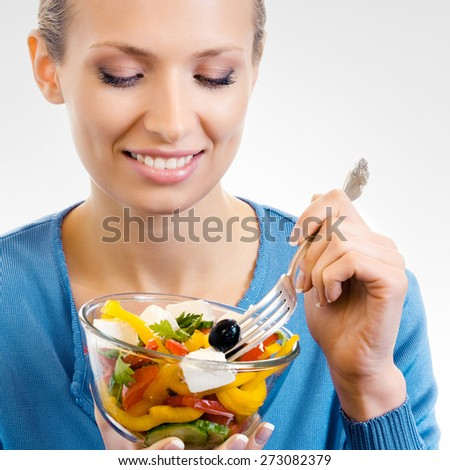 Cheerful young woman eating salad, on grey background - stock photo