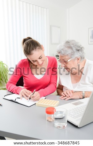 cheerful young woman helping an elderly woman with pills medical prescription  - stock photo