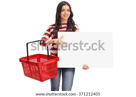 Cheerful young woman holding an empty shopping basket and pointing on a blank banner isolated on white background - stock photo