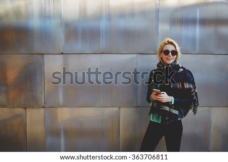 Cheerful young woman holding cell telephone and smile to the camera, cute female having fun while standing with mobile smart phone against big wall background with copy space for promotional content - stock photo