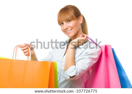 Cheerful young woman holding colorful shopping bags over white