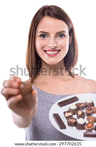 Cheerful young woman holding plate with delicious chocolate candies over white background. - stock photo