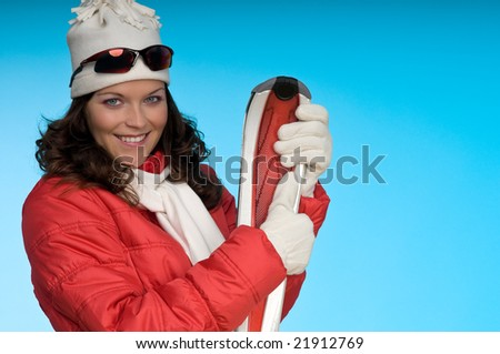 Cheerful young woman holding red skis on blue background