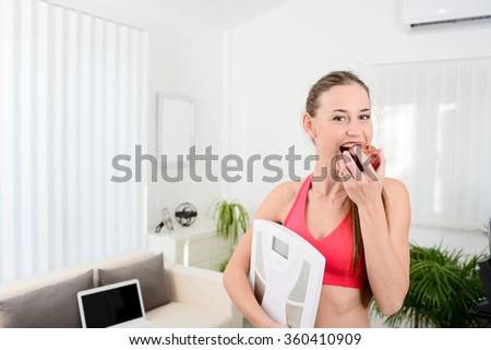 cheerful young woman holding scales and eating fruit weight loss program - stock photo