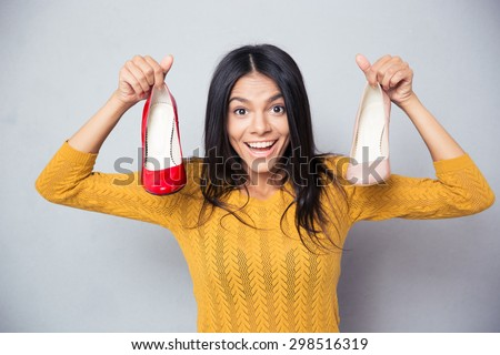 Cheerful young woman holding shoes over gray background and looking at camera - stock photo