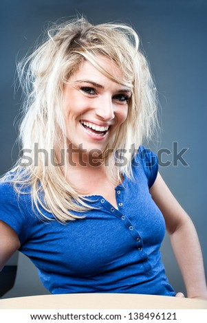 Cheerful young woman in blond hair posing with hands on her hips