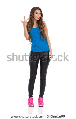 Cheerful young woman in blue shirt, black leather trousers, and pink sneakers standing and showing three fingers. Full length studio shot isolated on white. - stock photo