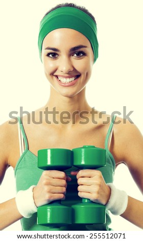 Cheerful young woman in green fitness wear exercising with dumbbells - stock photo
