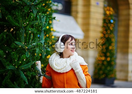 Cheerful young woman in orange coat walking on a street of Paris decorated for Christmas