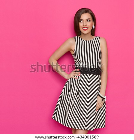 Cheerful young woman in striped dress posing with hand on hip and looking away. Three quarter length studio shot on pink background. - stock photo