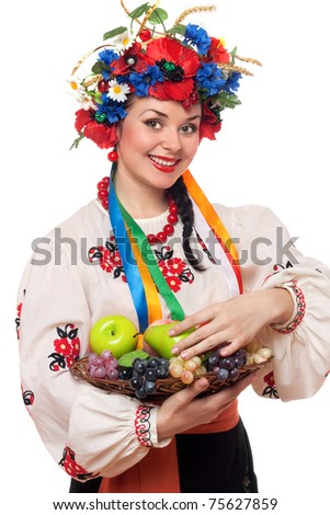 Cheerful young woman in the Ukrainian national clothes with fruit - stock photo