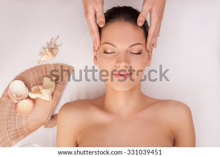 Cheerful young woman is lying and having head massage at spa. She is smiling with relaxation. The female hands of masseuse are massaging her temples - stock photo