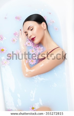 Cheerful young woman is sleeping in a bath with flowers. She is lying and smiling with happiness - stock photo