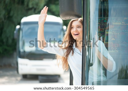Cheerful young woman is standing on doorsteps of a bus. She is looking through the doors and smiling. She is waving her arm and greeting with people - stock photo