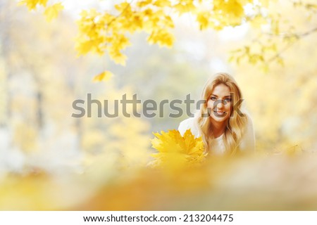 Cheerful young woman laying down on the ground covered with dry autumnal foliage in beautiful park - stock photo
