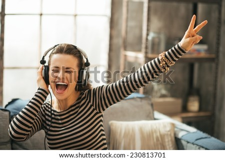 Cheerful young woman listening music in headphones in loft apartment - stock photo