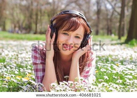 Cheerful young woman listening music with headphones and relaxing at beautiful spring day in the park. - stock photo