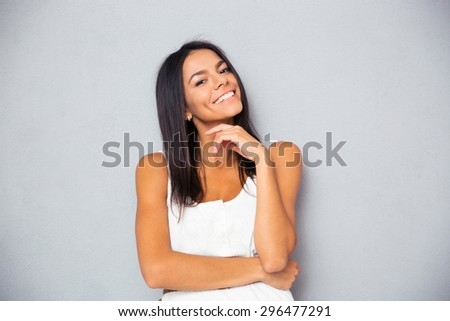 Cheerful young woman looking at camera over gray background - stock photo