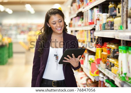 Cheerful young woman looking at digital tablet in shopping store - stock photo