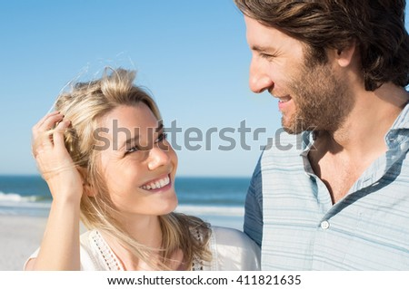 Cheerful young woman looking at her boyfriend with love at beach. Portrait of happy young couple at beach enjoying. Young couple romancing at seashore.  - stock photo