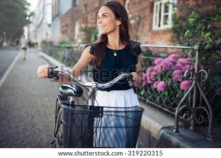 Cheerful young woman looking away while walking down the street with a bike. Female with a bicycle on city road looking at a view smiling. - stock photo