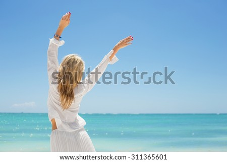 Cheerful young woman on the beach - stock photo