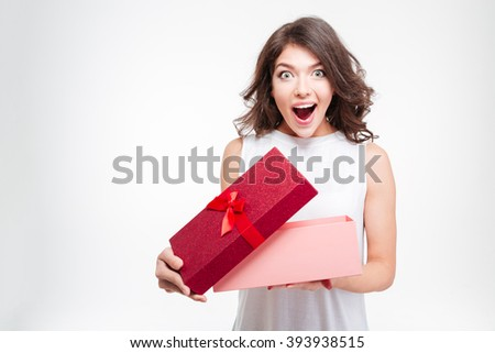 Cheerful young woman opening present box isolated on a white background - stock photo