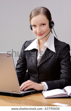 Cheerful young woman - Operator of call center with headset and laptop