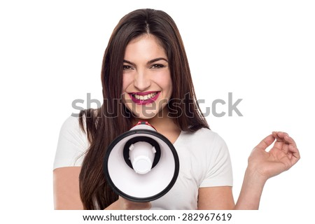 Cheerful young woman posing with loudhailer over white - stock photo