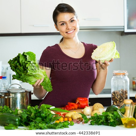 Cheerful young woman preparing vegetarian meal and smiling at home - stock photo