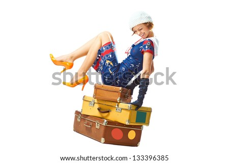 Cheerful young woman seat on the three suitcases on a white background - stock photo