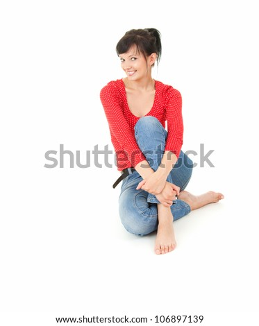 cheerful young woman sitting on the floor, full lenght, white background