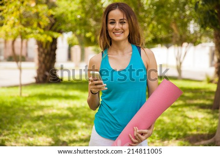 Cheerful young woman social networking on her mobile phone during her yoga practice