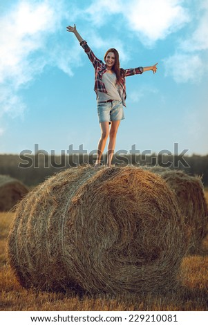 Cheerful young woman standing on a stack of hay in sunlight  - stock photo