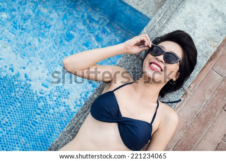 Cheerful young woman sunbathing by the pool - stock photo