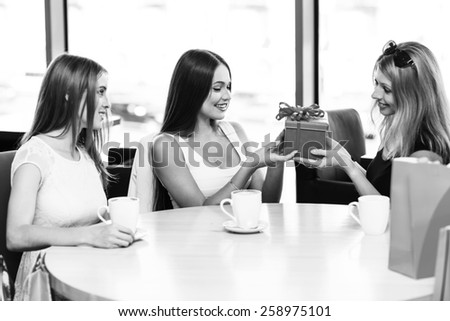 Cheerful young woman surprising friend with a gift in cafe - stock photo