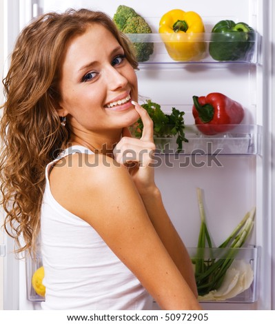 Cheerful young woman taking vegetables out of fridge - stock photo