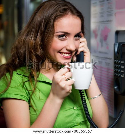 Cheerful young woman talking on the phone indoors