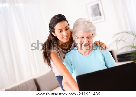 cheerful young woman teaching computer and internet to an elderly person - stock photo