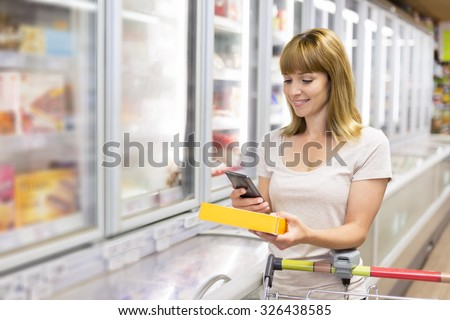 Cheerful young woman texting on mobile phone in supermarket - stock photo