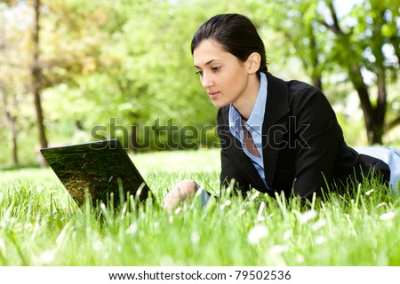 cheerful young woman using laptop on the green grass - stock photo