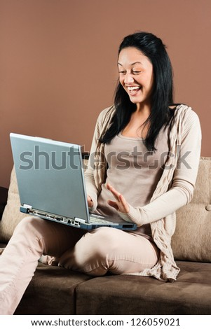 Cheerful young woman using laptop,Young woman with laptop - stock photo