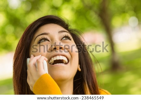 Cheerful young woman using mobile phone in the park - stock photo