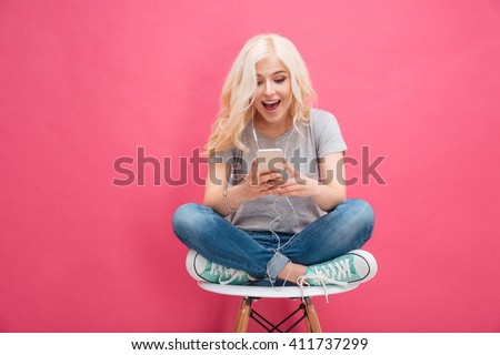 Cheerful young woman using smartphone with headphones over pink background - stock photo