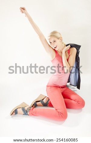 Cheerful young woman wearing red pants, arm raised - stock photo