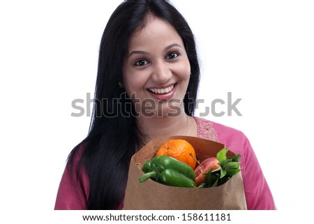 Cheerful young woman with a grocery bag full of fruits and vegetables - stock photo