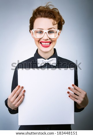 Cheerful young woman with blank white board on gray isolated - stock photo